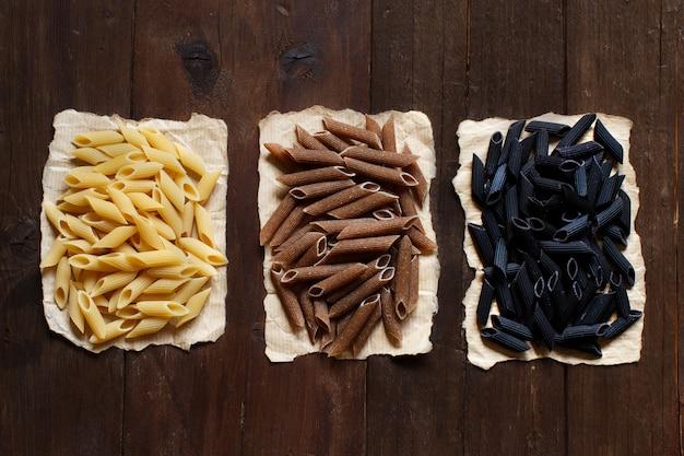 Trois types de pâtes penne sur une table en bois