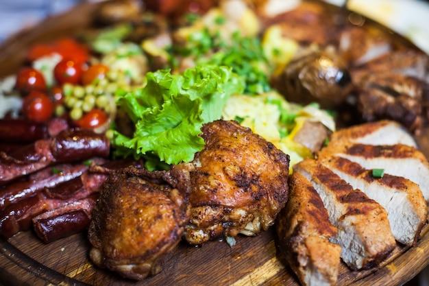 Trois types de viande avec laitue et tomates allongées sur une planche de bois