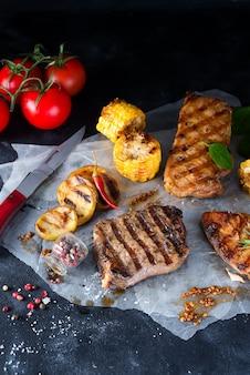Trois types de viandes grillées avec des légumes et des épices sur papier