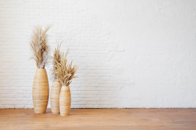 Trois vases en osier avec de l'herbe sèche de la pampa contre un mur de briques texturées blanches.