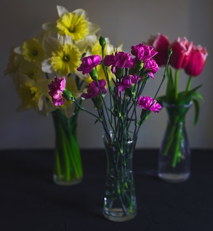 Trois vases en verre d'oeillets, jonquilles, tulipes