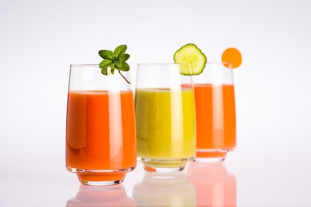 Trois verre de jus de légumes végétalien bio coloré sur fond blanc