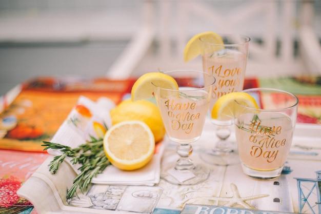 Trois verres d'agrumes sur un plateau. sur les verres de quartiers de citron