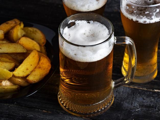 Trois verres de bière légère et pommes de terre de pays sur une table sombre