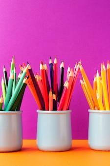 Trois verres en céramique avec des crayons de couleur. retour au concept d'école. contexte de l'éducation.