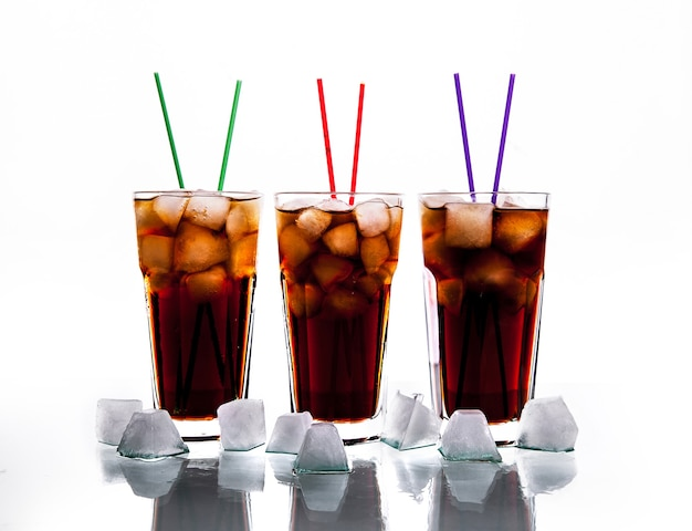 Trois verres de cola avec de la glace et des pailles sur un fond blanc.