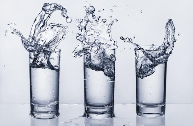Trois verres avec des éclaboussures d'eau. éclaboussures d'eau. sortie d'eau.