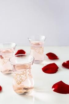 Trois verres de limonade rose rafraîchissante avec des pétales de fleurs de rose sur fond blanc.