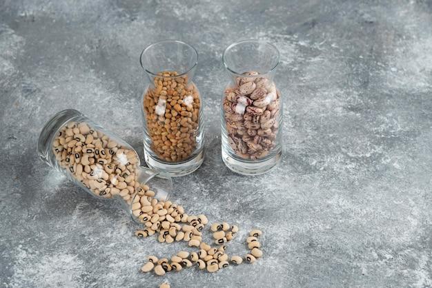 Trois verres de pot avec des haricots non préparés sur une table grise.