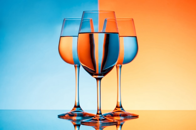 Trois verres à vin avec de l'eau sur fond bleu et orange.
