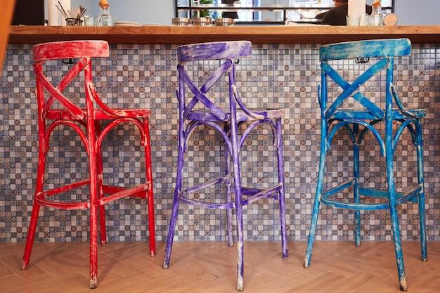 Trois vieilles chaises multicolores debout dans une rangée près du bar
