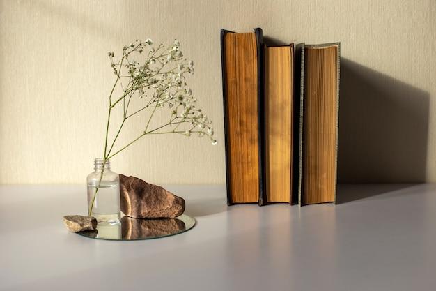 Trois vieux livres une branche d'une fleur de gypsophile blanche debout sur une bouteille