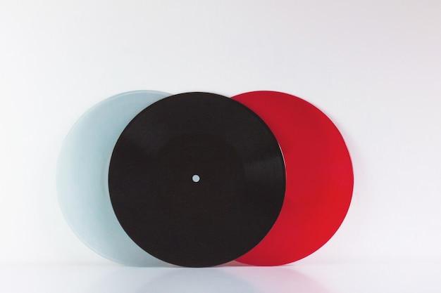 Trois vinyles, bleu, noir et rouge, sur blanc, avec espace