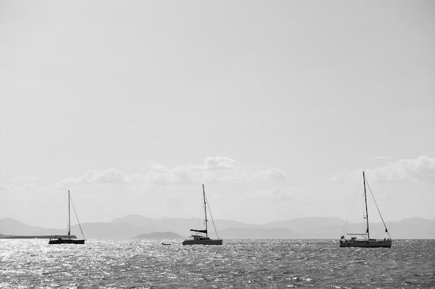 Trois voiliers dans la mer près de l'île d'egine, grèce. photographie noir et blanc, paysage marin