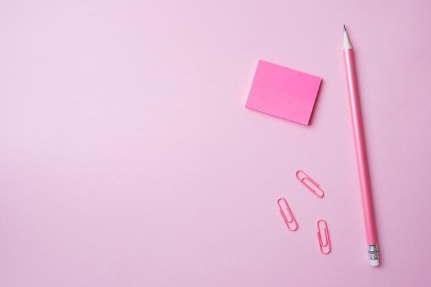 Trombone bloc-notes rose et un crayon sur rose