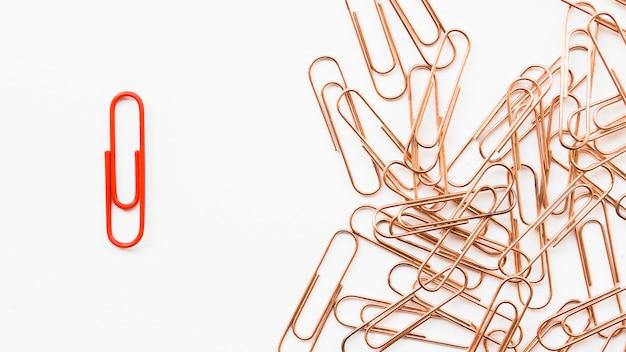 Trombone rouge unique à côté de tas de cuivre
