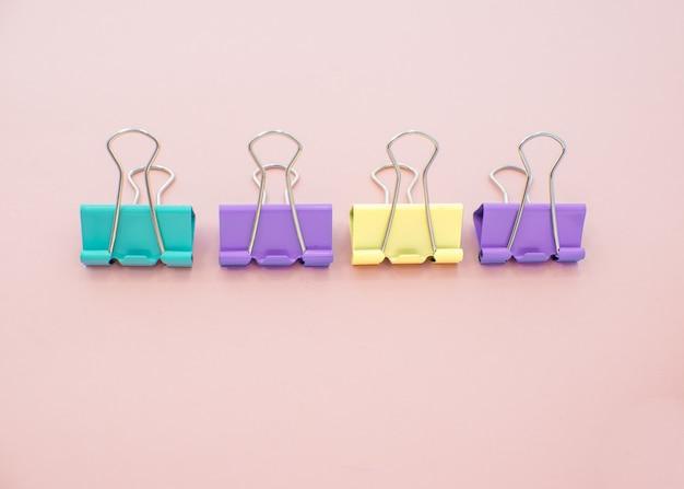Trombones colorés sur fond rose. papeterie de bureau