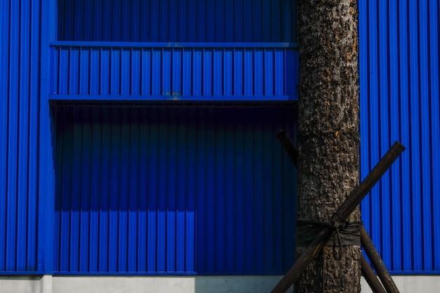 Tronc d'arbre devant le mur bleu texturé