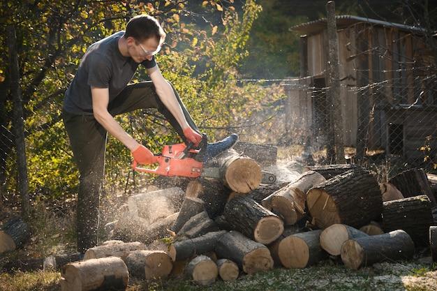 Tronçonneuse qui se dresse sur un tas de bois de chauffage dans la cour