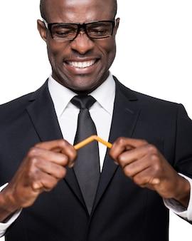 Trop de stress. furieux jeune homme africain en tenue de soirée brisant le crayon et grimaçant en se tenant debout isolé sur fond blanc