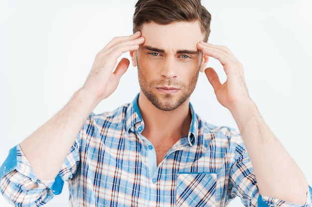 Trop de stress. jeune homme frustré touchant la tête avec les doigts et regardant la caméra