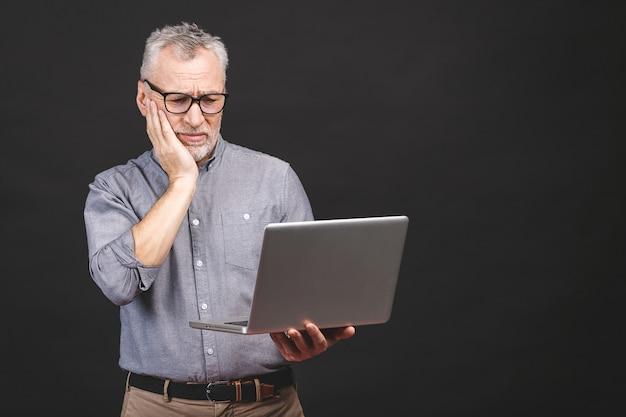 Trop de travail à faire. fatigué homme âgé senior en colère avec ordinateur portable
