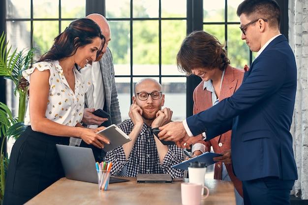 Trop de travail mise au point sélective du jeune homme d'affaires entouré de collègues chacun propose un projet demande l'approbation ou la signature.