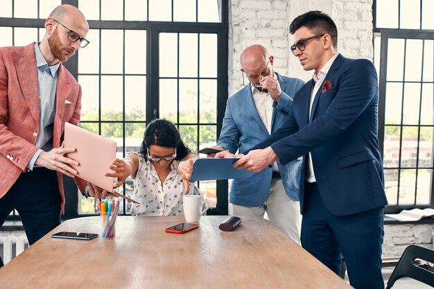 Trop de travail mise au point sélective de la jeune femme d'affaires entourée de collègues chacun propose un projet demande l'approbation ou la signature.