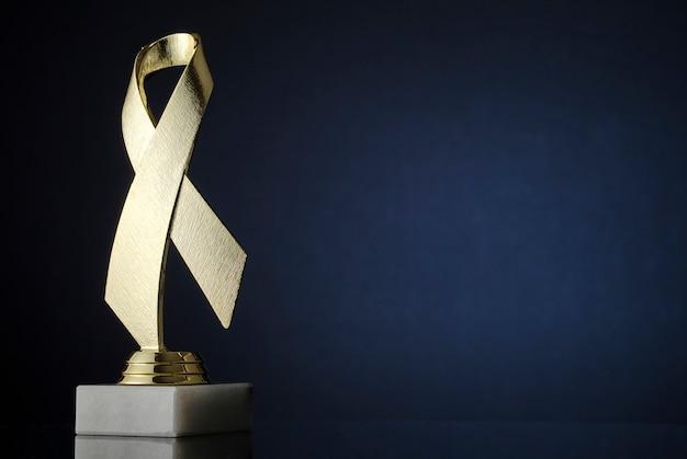 Trophée du ruban d'or texturé symbolique sur dégradé bleu