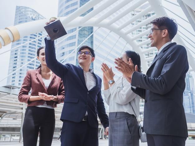 Trophée d'or de l'équipe commerciale gagnante, hommes et femmes d'affaires heureux de réussir dans leur travail