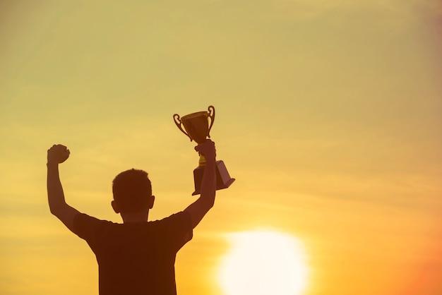 Trophée sport silhouette meilleur homme gagnant trophée de la victoire pour un défi professionnel. le concours de champion de la coupe du trophée d'or remporte le prix de récompense du sport. défi sportif gagnant-gagnant