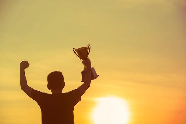 Trophée sport silhouette meilleur homme mains qui le trophée de la victoire du gagnant pour le défi professionnel.