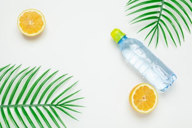 Tropic laisse et bouteille l eau sur jaune. eau infusée aux fruits detox.