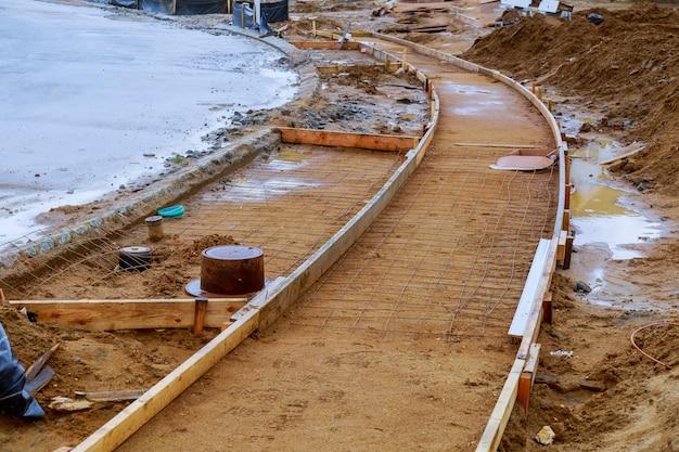 Trottoir en construction, installation d'une bordure de béton en cours.