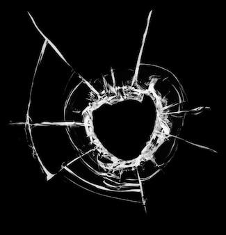 Trou de balle dans le verre. isolé sur un fond noir.
