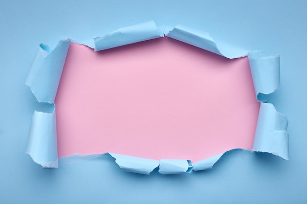 Trou dans le papier bleu. déchiré. rose . abstrait .