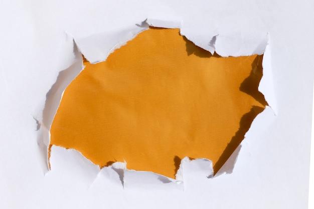 Un trou dans le papier avec un fond d'or en dessous. modèle de texte sur une bannière.