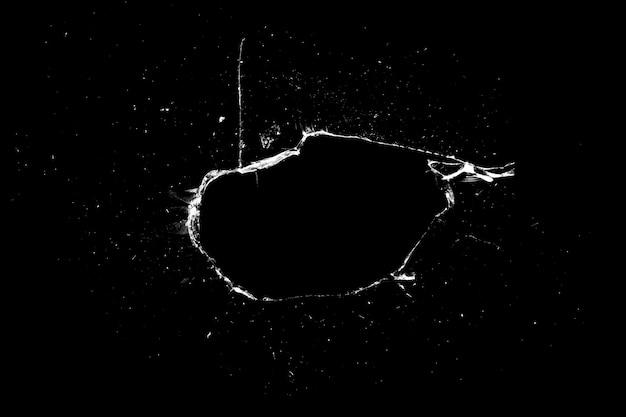 Trou dans le verre avec des fissures isolées sur fond noir. texture pour la conception