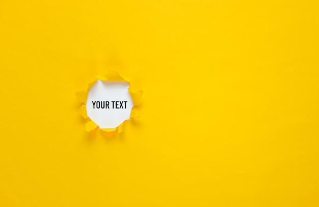 Trou déchiré dans du papier jaune. vue de dessus. concept d'entreprise minimaliste. copier l'espace