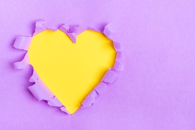Trou en forme de coeur jaune à travers du papier violet