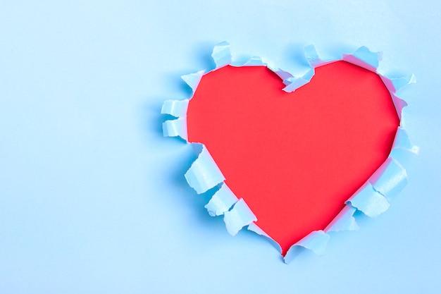 Trou en forme de coeur rouge à travers du papier bleu