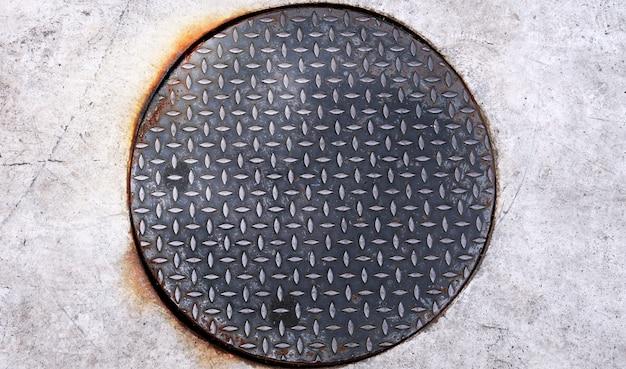 Trou d'homme rond rouillé fait d'une plaque d'acier damier d'une barre