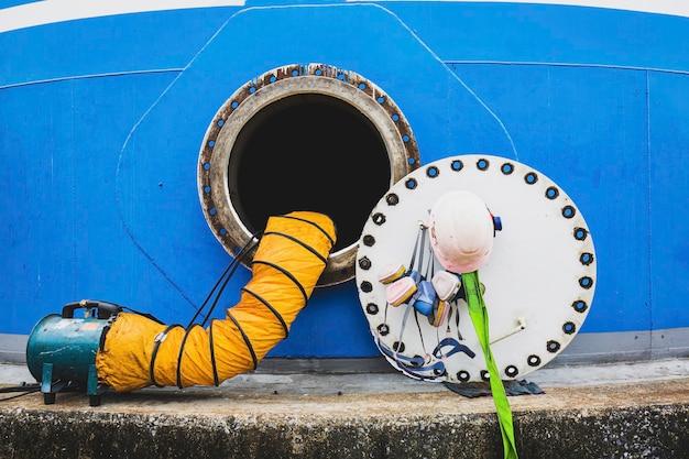 Trou d'homme rouillé ouvert sur le réservoir de carburant bleu et souffle d'air frais dans l'espace confiné du réservoir de stockage d'huile