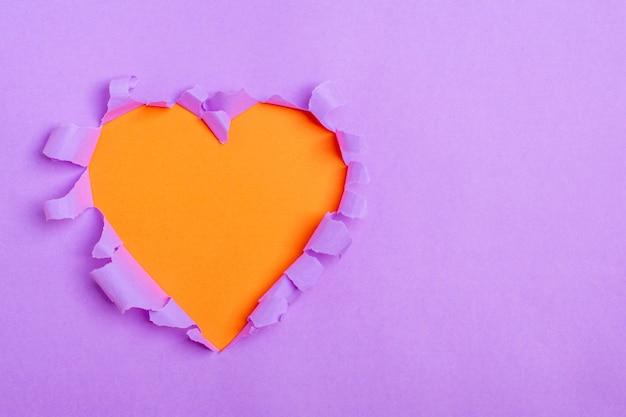 Trou orange en forme de coeur à travers du papier violet