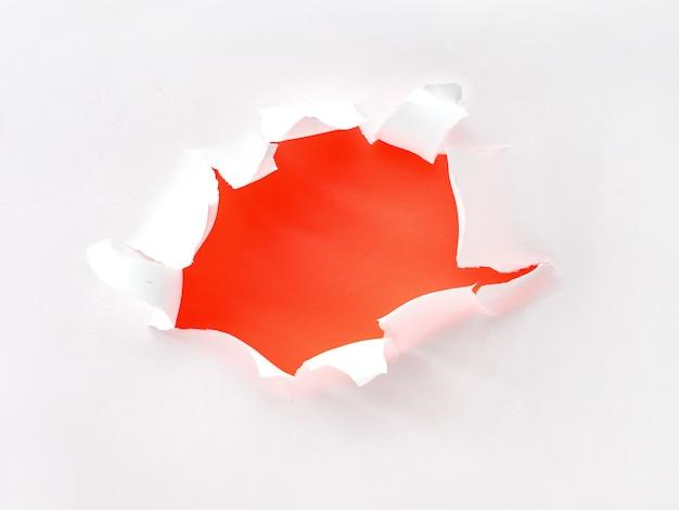 Trou de papier déchiré dans du papier blanc sur un orange, à plat avec copie-espace
