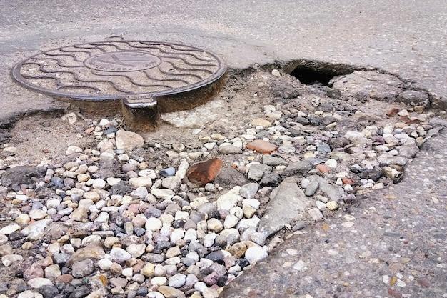 Trou de route asphalté détruit à côté du trou d'homme d'égout sanitaire