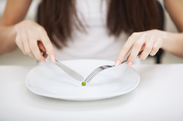 Trouble de l'alimentation. fille tient une assiette et essaye de mettre un petit pois sur la fourchette
