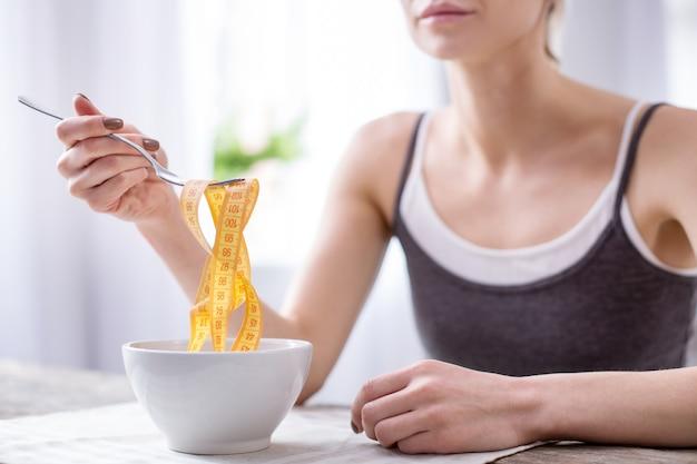Trouble de l'alimentation. gros plan d'une bande d'un centimètre jaune détenue par une femme souffrant d'un trouble de l'alimentation