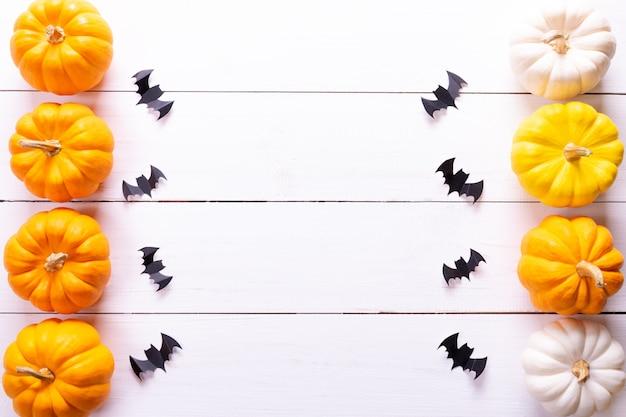 Troupeau de chauves-souris en papier noir et citrouilles fraîches sur tableau blanc
