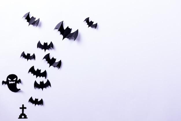 Troupeau de chauves-souris en papier noir et fantôme sur surface blanche